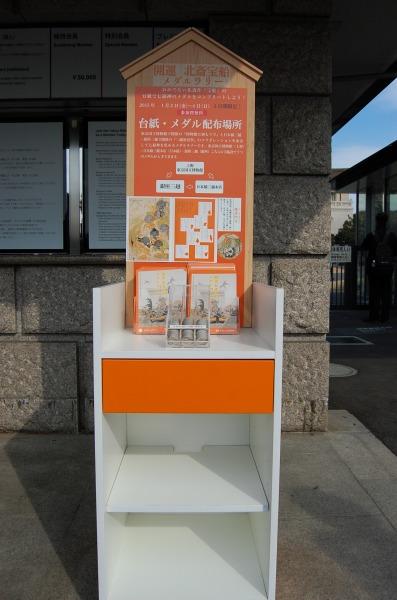 東京国立博物館の正門プラザに設置された「北斎宝船メダルラリー」の台紙とメダルの配布台